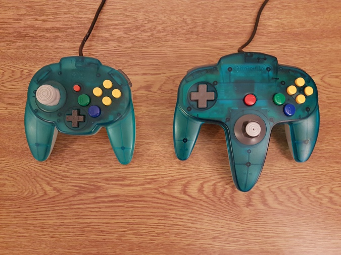 A photo comparing the size of an N64 Hori Mini Pad to the official Nintendo 64 Controller