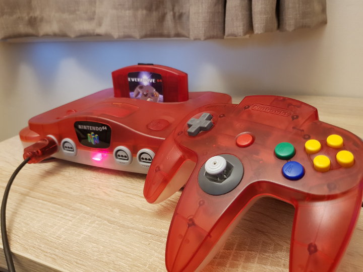Red-white transparent N64 with red EverDrive 64 V3 flashcart.