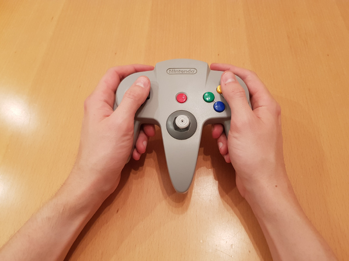 Holding the N64 controller by the outer prongs to use the D-Pad and C-buttons.