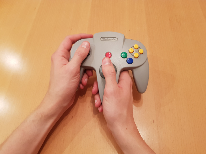 Holding the left and middle handles of the N64 controller
