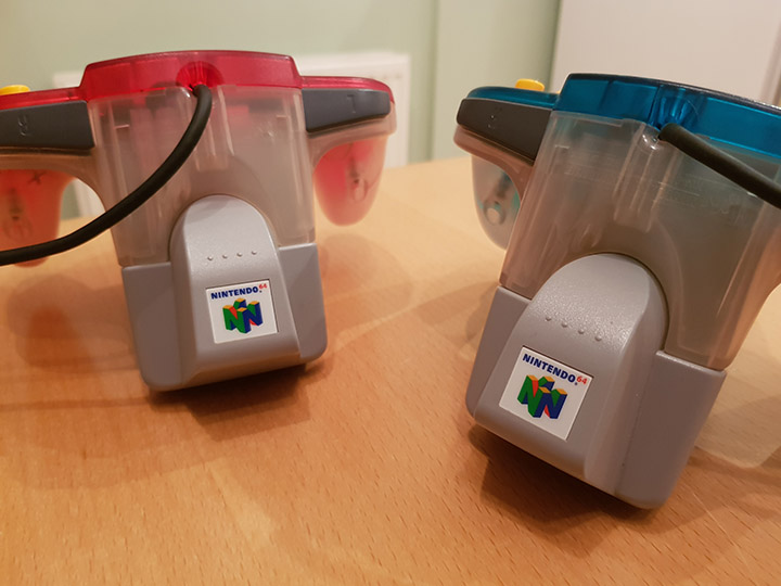 Two N64 controllers with Rumble Paks inserted into them.