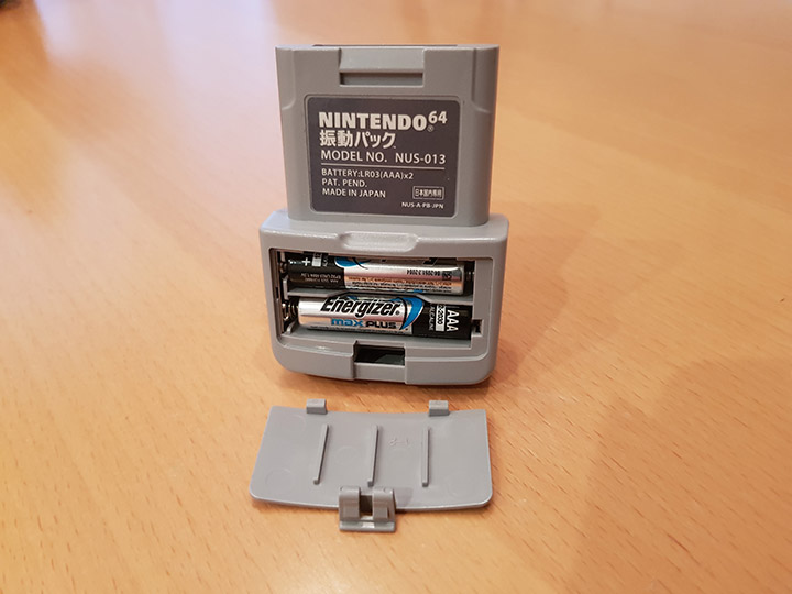 An N64 Rumble Pak with the battery cover removed.