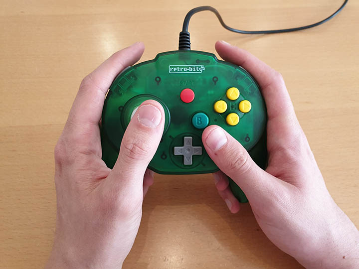 Holding the Tribute 64 controller for N64 in both hands