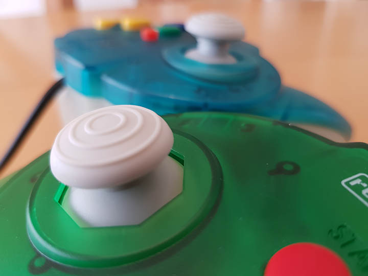 A photo showing the Retro-Bit Tribute 64 controller's joystick and that of the N64 Hori Mini Pad.