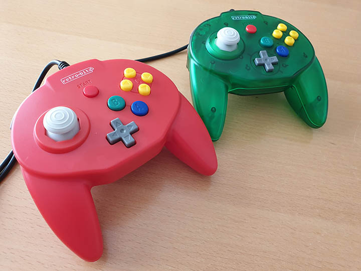 Retro-Bit Tribute 64 controllers in red and forest green colours.