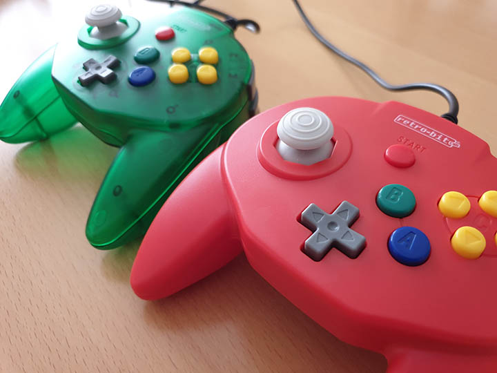 Forest green and red Retro-Bit Tribute 64 controllers side by side on a table.