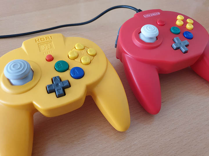 A comparison shot between the N64 Hori Mini Pad and the Retro-Bit Tribute 64 controller.