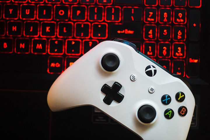 An Xbox One controller resting on top of a neon keyboard.