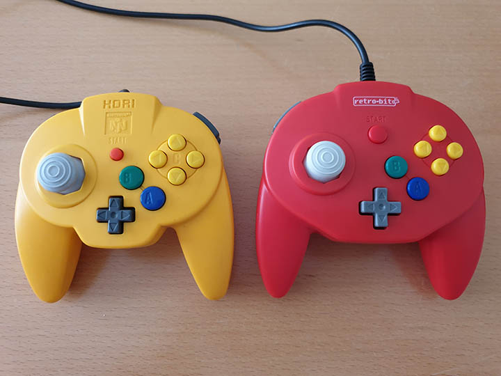 A photo comparing the shape and size of the Tribute 64 controller and the N64 Hori Mini Pad.