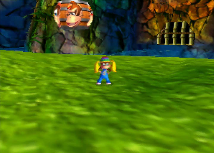 Tiny Kong stands next to a tag barrel in Donkey Kong 64.
